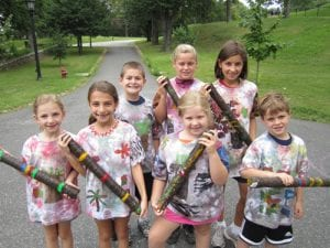 Children show T-shirts and rain sticks made in summer workshops